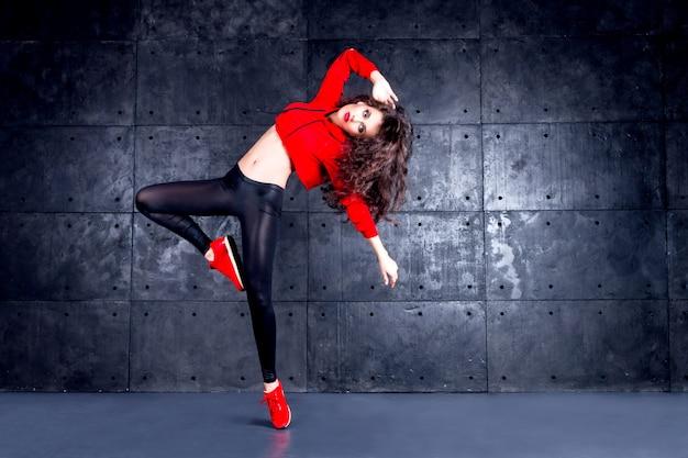 Garota dançando na frente da muralha urbana.