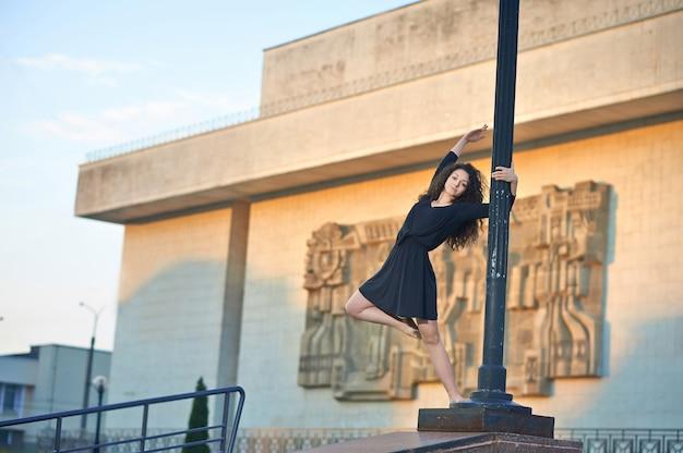 Garota dançando no pilar da lâmpada perto da fachada do edifício interessante.