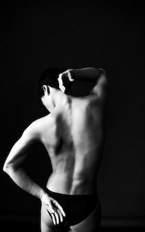 Garota dançarina nua de costas em uma parede preta