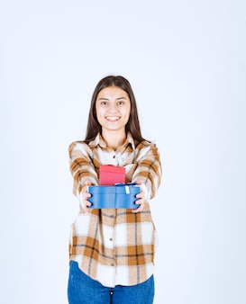 Garota dando dois presentes na parede branca.