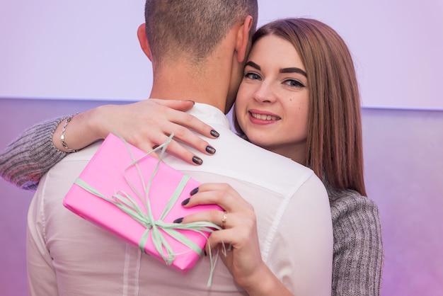 Garota dando o namorado presente tiro do estúdio. conceito do dia dos namorados.