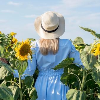 Garota dando um passeio em um campo com flores do sol