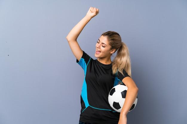 Garota de adolescente de jogador de futebol loira sobre parede cinza, celebrando uma vitória