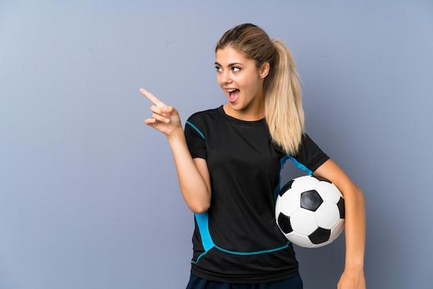 Garota de adolescente de jogador de futebol loira surpreso e apontando o dedo para o lado