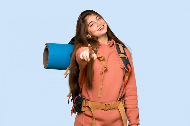 Garota de alpinista aponta o dedo para você com uma expressão confiante em azul
