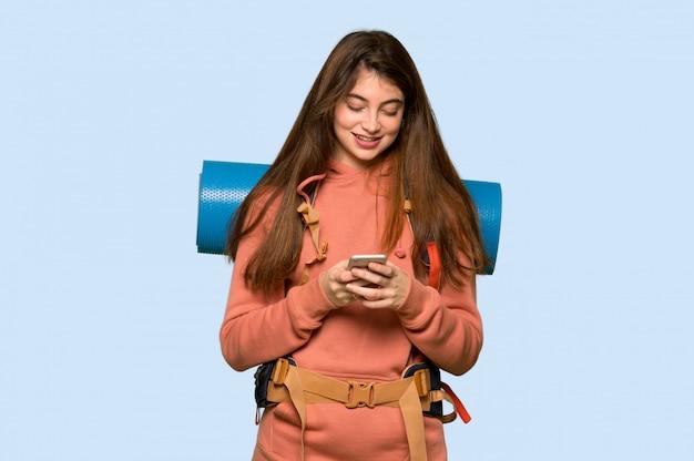 Garota de alpinista, enviando uma mensagem com o celular em azul