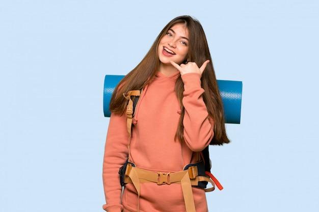 Garota de alpinista fazendo gesto de telefone. me ligue de volta assinar em azul