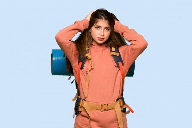 Garota de alpinista leva as mãos na cabeça porque tem enxaqueca no azul