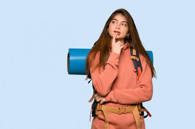 Garota de alpinista tendo dúvidas enquanto olhando para cima em azul