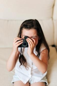 Garota de alto ângulo tirando fotos com a câmera