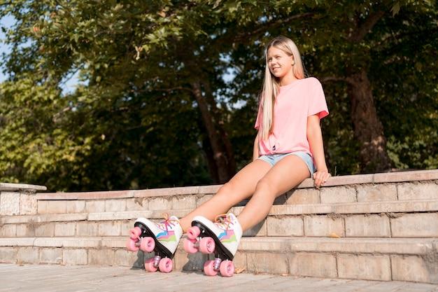 Garota de ângulo baixo usando patins