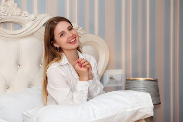 Garota de aparência eslava em uma camisa branca sexy na cama em um quarto de hotel