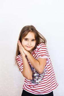 Garota de aparência europeia em um fundo branco em uma camiseta com um coração, dia dos namorados, coração, amantes, amor e família