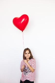 Garota de aparência européia, sobre um fundo branco, segurando um balão em forma de coração,