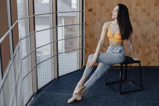 Garota de aptidão atraente jovem sentada na cadeira perto da janela