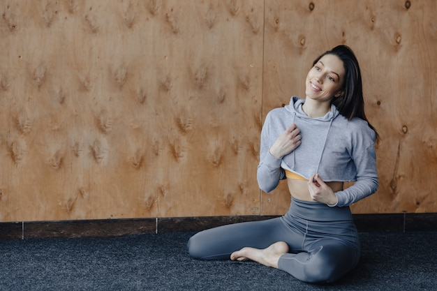 Garota de aptidão atraente jovem sentada no chão, descansando em aulas de ioga