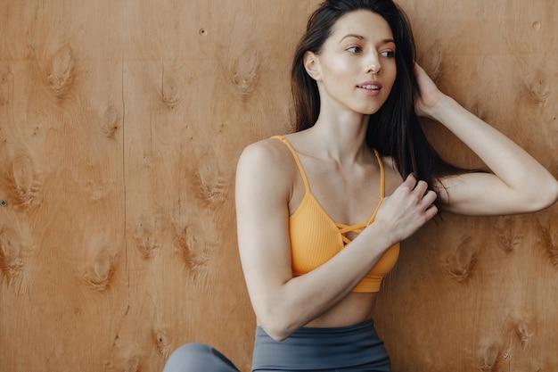 Garota de aptidão atraente jovem sentada no chão perto da janela