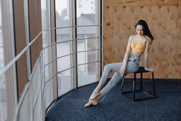 Garota de aptidão atraente jovem sentado na cadeira perto da janela, descansando em aulas de ioga