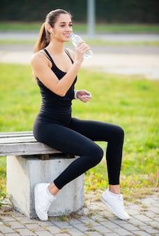 Garota de aptidão. jovem mulher bonita no sportswear bebendo água no parque