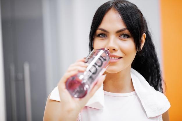 Garota de aptidão. jovem mulher bonita no sportswear bebendo água