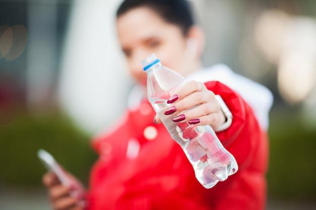 Garota de aptidão. mulher do esporte que guarda a garrafa com água. estilo de vida saudável na cidade grande.