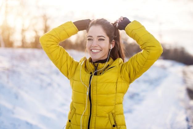 Garota de aptidão trabalhadora sorridente com fones de ouvido no sportswear de inverno, amarrando um rabo de cavalo fora na natureza de neve.