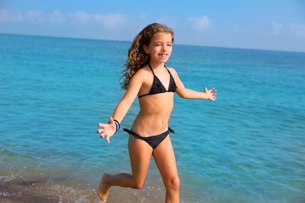 Garota de azul praia garoto com biquíni pulando e correndo