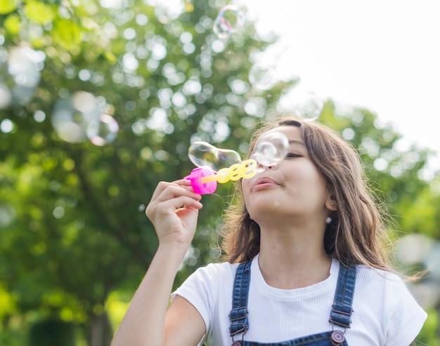 Garota de baixo ângulo fazendo bolhas de sabão