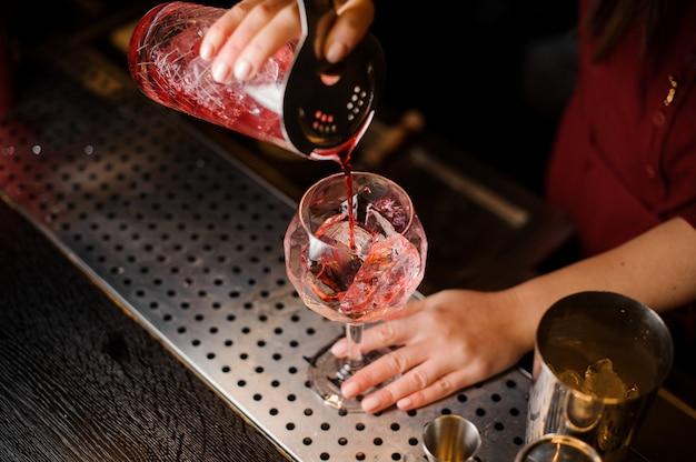 Garota de barman, derramando um coquetel líquido vermelho no copo