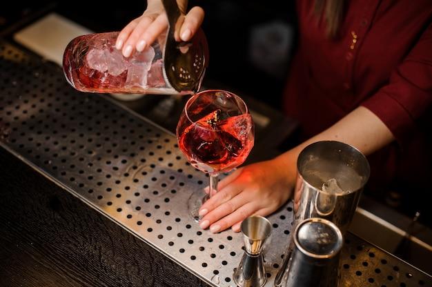 Garota de barman derramando um coquetel vermelho gelado