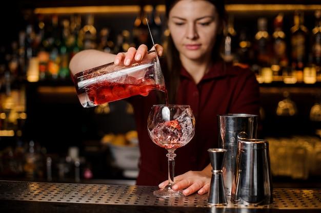 Garota de barman derramando um delicioso coquetel vermelho