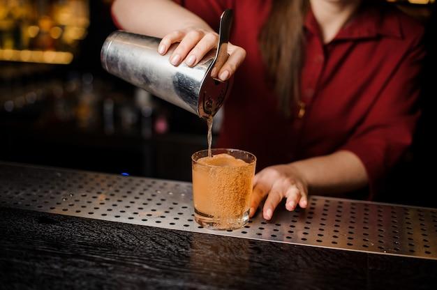 Garota de barman encher copo de coquetel no balcão do bar
