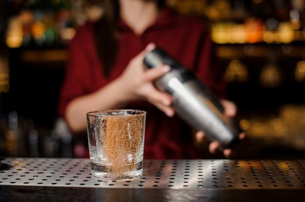 Garota de barman fazendo coquetel adorável no balcão do bar
