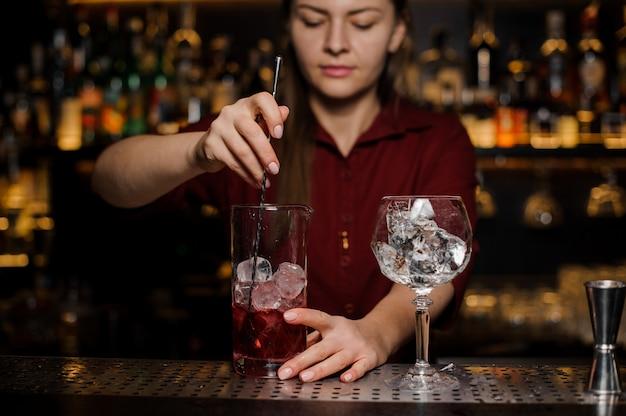 Garota de barman fazendo um coquetel vermelho claro fresco