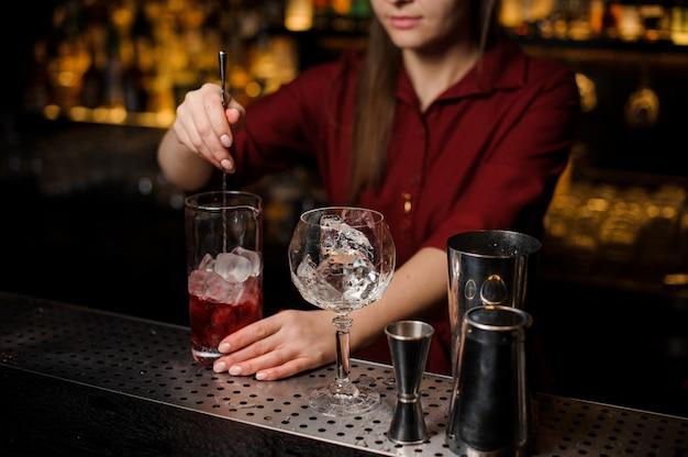 Garota de barman mexendo um coquetel vermelho claro