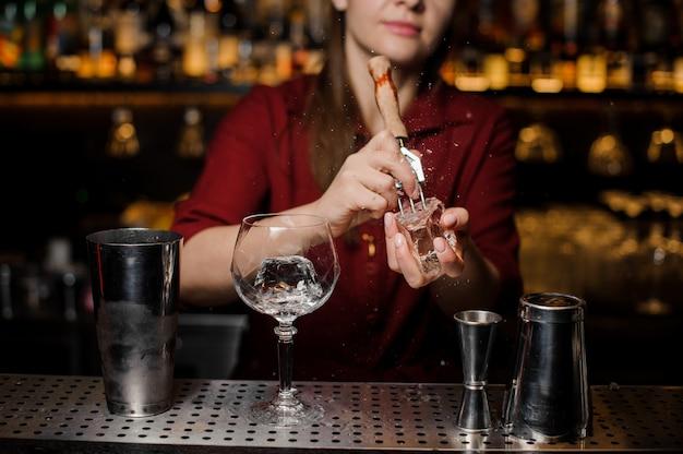 Garota de barman quebrando um pedaço de gelo para o coquetel