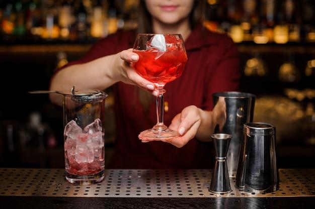 Garota de barman servindo um coquetel vermelho claro