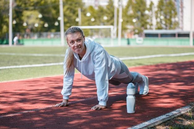 Garota de beleza squatting.young fazer exercícios no estádio