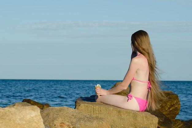 Garota de biquíni com sorvete na mão, falando ao telefone nas rochas perto do mar