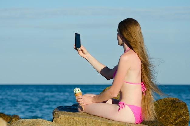 Garota de biquíni com sorvete na mão na praia rochosa faz telefone selfie contra o mar