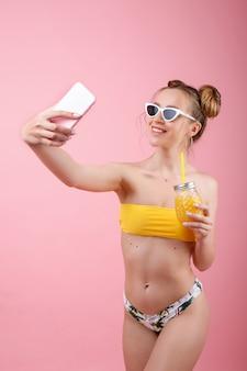 Garota de biquíni e óculos com um copo de suco leva uma selfie no telefone. clima de verão