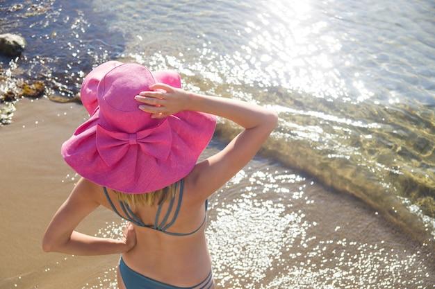 Garota de biquíni e um chapéu à beira-mar.