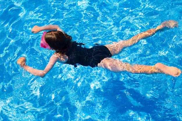 Garota de biquíni garota nadando na piscina de azulejos azuis no verão