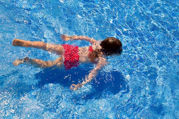 Garota de biquíni garota nadando na piscina de azulejos azuis