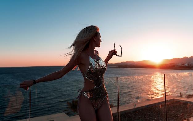 Garota de biquíni lindo admirando um belo pôr do sol