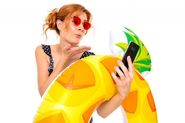 Garota de biquíni manda beijos pelo telefone enquanto segura um círculo de natação em uma parede branca