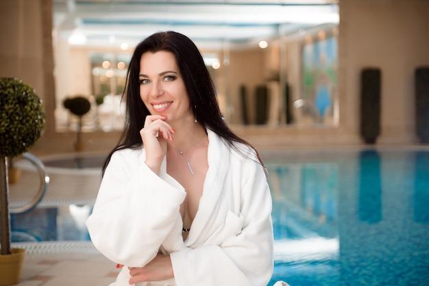 Garota de biquíni perto da piscina no salão spa dia resort