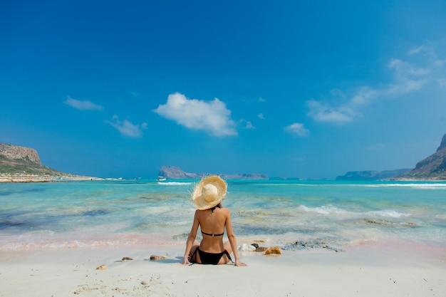 Garota de biquíni preto e com chapéu na praia de balos