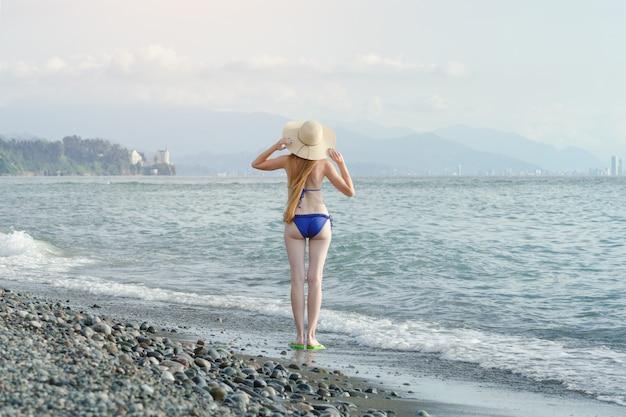 Garota de biquíni terno e chapéu está de pé pelo mar. vista traseira