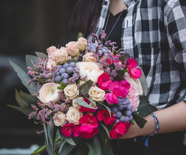 Garota de blusa xadrez com buquê de flores na mão